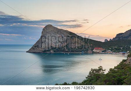 Large headland in the sea near the resort town in the Bay at sunset. Cape Chyken Peninsula of Crimea resort Noviy Svet