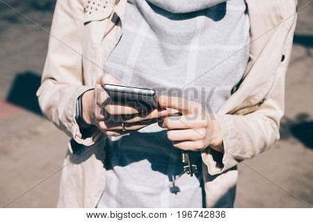 Young Woman In A Beige Jacket Holds A Mobile Phone