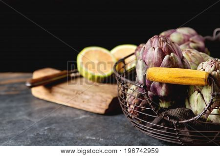 Baby Ripping Organic Artichokes With Lemon. Food For A Vegan And