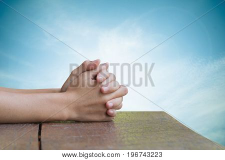Hands on an old wooden table Natural background blurred sky pretty bright. Prayer to God.