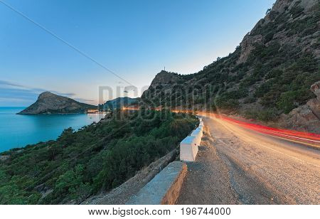 The serpentine in the mountains with the light trace from a passing car in twilight on a background of mountains headland and sea beyond.