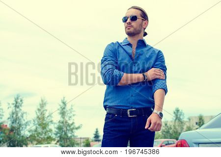 Handsome young man in jeans clothes stands on a city street. Men's fashion.