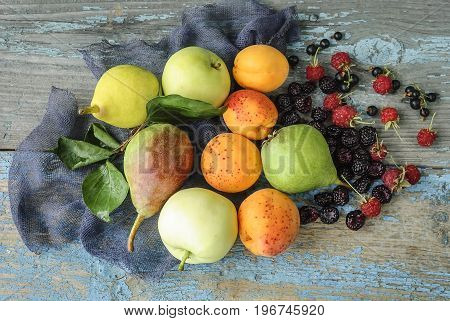 Assorted fresh fruits and berries on a wooden surface