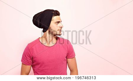 Good-looking brunette guy standing dressed in pink t-shirt and brown hat looking away.