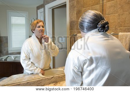 Old Woman Looking At Younger Reflection In Mirror