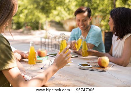 Image of happy young multiethnic friends students outdoors drinking juice and talking with each other. Looking aside.