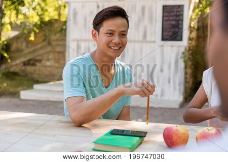 Photo of smiling young multiethnic group of friends students talking with each other outdoors. Looking aside.