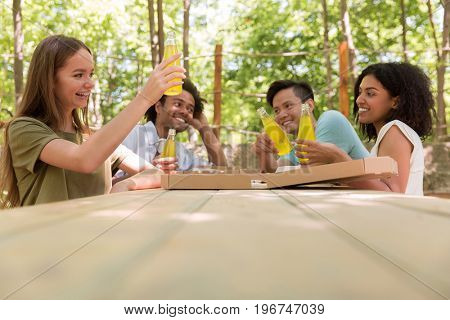 Image of cheerful young multiethnic friends students outdoors drinking juice eating pizza and talking with each other. Looking aside.