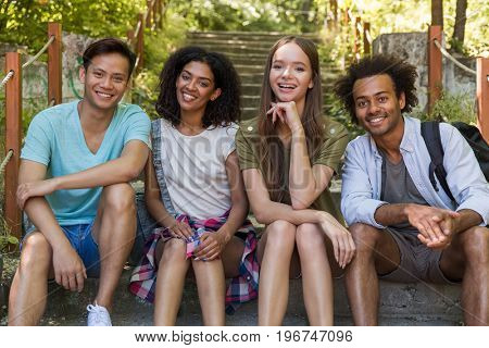 Picture of young cheerful multiethnic friends students outdoors sitting on ladder. Looking camera.