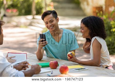Picture of cheerful young multiethnic group of friends students talking with each other outdoors using mobile phone. Looking aside.