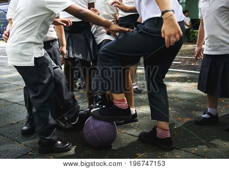 Group of diverse kindergarten students playing soccer together