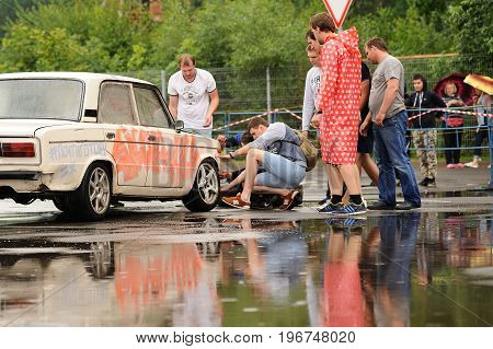 Orel Russia July 22 2017: Dynamica car festival. Young people looking at old Soviet car VAZ Lada with graffiti near big water puddle at rainy day