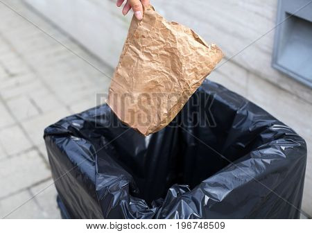 Closeup hand throwing a crumpled paper bag in the trash on street