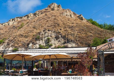 Outdoors summer cafe near or under the sandstone hill in balchik town on black sea coast.