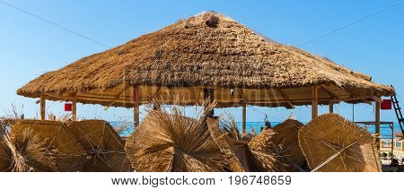 Straw roof on beach bungalow construction and many straw parasol panoramic view.