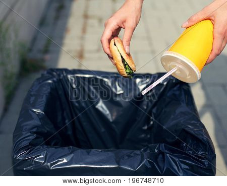 Fast Food And Unhealthy Eating Concept - Hand Throwing A Burger With A Plastic Cup In The Trash On T