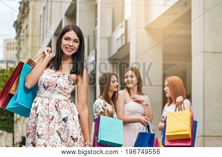 Portrait of beautiful smiling woman posing after shopping with her friends