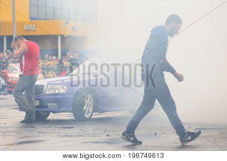 Orel Russia July 22 2017: Dynamica car festival. Man walking in burning wheel smoke clouds background