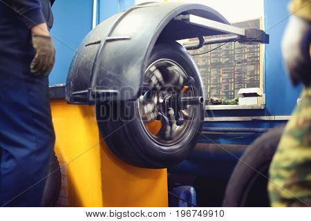 Workers And Process Tire Service, Tyre Wheel Of Car In Motion