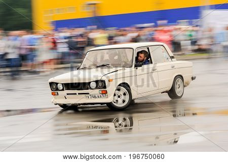 Orel Russia July 22 2017: Dynamica car festival. Tuned white vintage Russian VAZ Lada car riding in water puddles motion blur