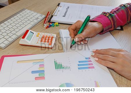 Business plan calculator dollar banknote on the table. Savings finances economy Business and home concept - Female with calculator counting money and making notes at home