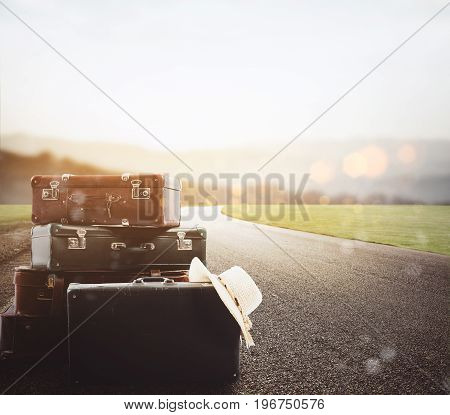 Luggage resting on asphalt with background a road at sunset