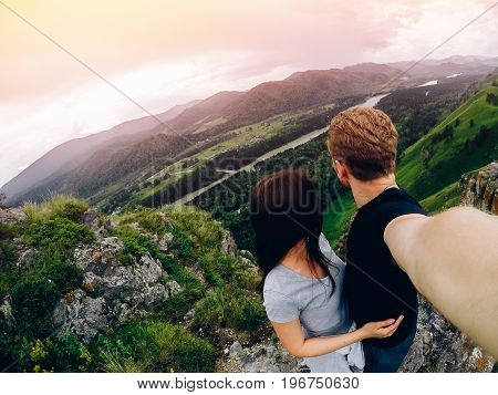 Guy and girl tourists are happy, hug and do selfie on action camera on background of mountains, forests. Concept love and travel. Russia, Altai Mountains.