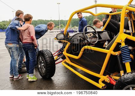 Orel Russia July 22 2017: Dynamica car festival. People look at buggy car with interest at rainy day
