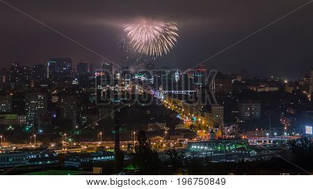 Fireworks exploding high in the sky with clouds over night city.