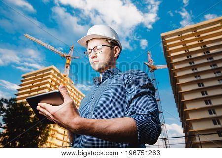 builder is a man in a protective helmet, glasses and a tablet computer in the hands amid a crane, a multi-storey building outside, on the street. Concept construction, business, technology. Sun shimmer