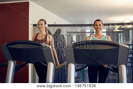 Attractive young woman with wireless headphones standing on treadmill in the gym looking at camera and smiling with copy space