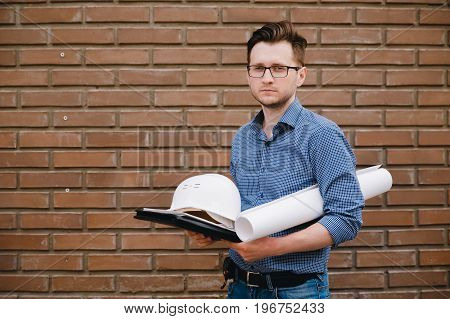 Male construction builder worker - foreman is an engineer in a protective helmet, glasses on the background of building a house with a crane. Concept calculation of construction time and cost.
