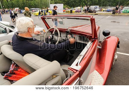 Orel Russia July 22 2017: Dynamica car festival. Senior man sitting in red Fiat cabriolet closeup