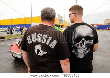 Orel Russia July 22 2017: Dynamica car festival. Men standing their backs to camera in t-shirts Russia and skull closeup