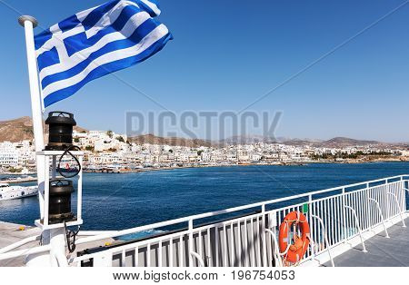 The harbor of Naxos island seen from a ferry boat with a Greek flag
