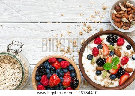 homemade granola with greek yogurt nuts and fresh berries in a bowl with cereal in jar for healthy breakfast over white wooden background. top view