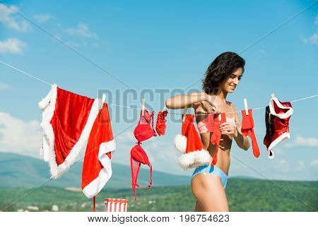 New year girl on sunny blue sky. Laundry and dry cleaning. Santa claus girl hanging clothes for drying. Xmas red costume on rope with pin. Christmas woman with happy face outdoor.