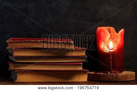 Vintage Books And A Candle On A Dark Background