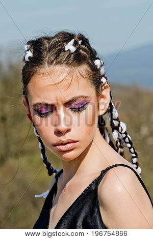 Beauty and fashion. Cosmetics and skincare. Hairdresser and barber. Woman has stylish hair with rope. Girl with fashionable makeup on blue sky background.