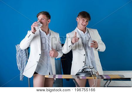 Macho winking and pointing finger. Man drinking from cup in dressing room. Businessmen wearing shirts jackets and underpants. Ironing board with iron and clothes rack on blue background. Fashion.