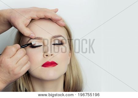 Girl With Closed Eyes And Red Lips Getting Makeup
