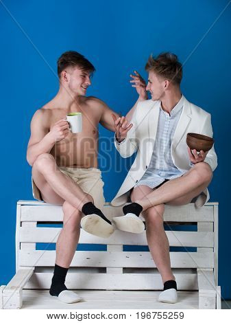 Happy men on wooden bench on blue background. Macho with muscular torso wrapped in towel. Businessman wearing shirt jacket and underpants. Drinking and healthy dieting. Fashion and fitness concept.
