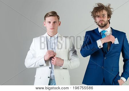 Two Businessmen Standing On Grey Background