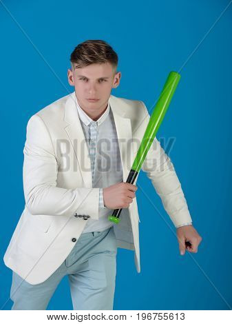 Power and energy concept. Fashion and sport. Businessman wearing white jacket shirt and pants. Man holding green bat. Baseball player posing on blue background.