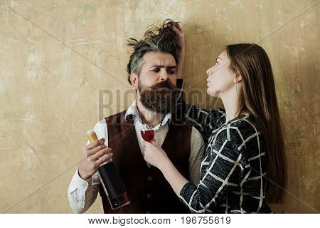 Girlfriend with glass touching messy hair of boyfriend with bottle of wine. Girl or woman and man or hipster with beard on beige wall. Couple in love. Alcohol and convive. Bad habits