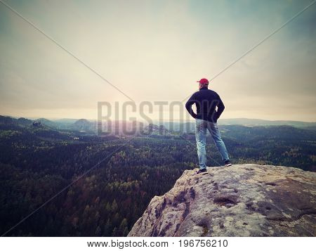 Man Hiker On Sharp Cliff. Hiker Climbed Up To Peak Enjoy View. Man  Watch Over Morning Valley