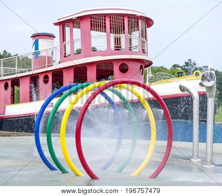 Urban Splash Pad And Park With Old Fashioned Boat Play Equipment And Water Spraying From Rings And F