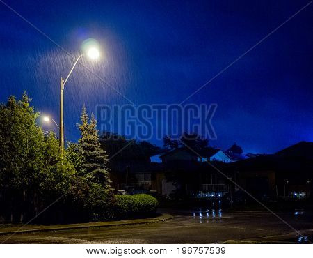 Heavy Rain Falling On Residential Street, Illuminated By Lamp Post, Blue Dark Cloudy Storm Sky