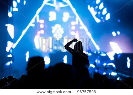 Crowd Of People With Arms Outstretched Partying At An Edm Concert