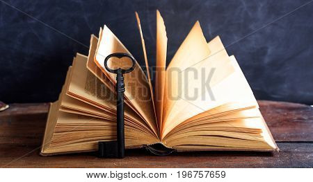 Old Book And A Key On A Wooden Desk